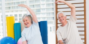 Portrait of happy senior couple doing stretching exercise in gym
